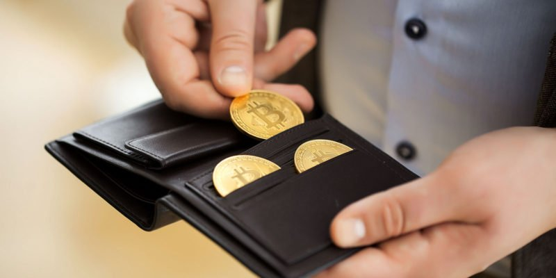 Persoon met bitcoins in portemonnee